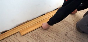 Person installing bamboo flooring against wall
