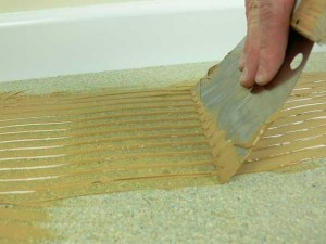 Flooring adhesive being applied onto a sub floor